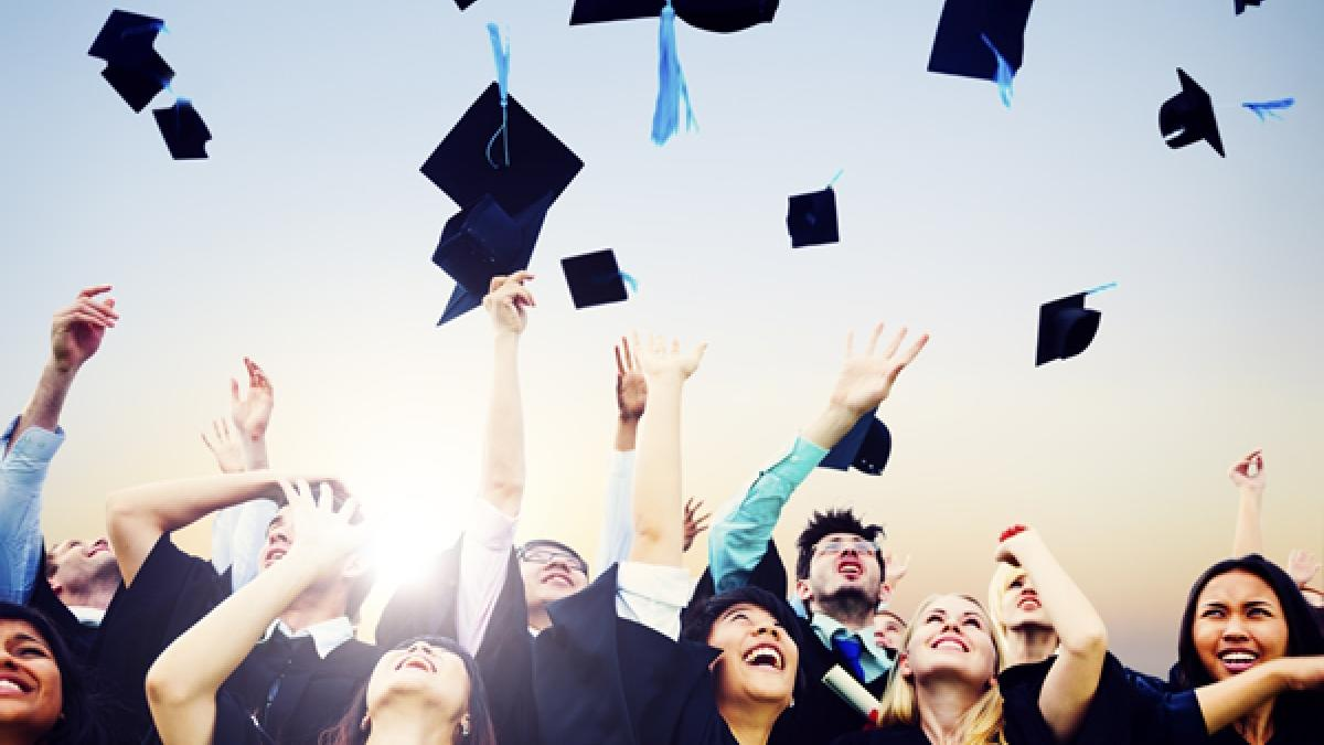 Graduates throwing mortar boards in the air